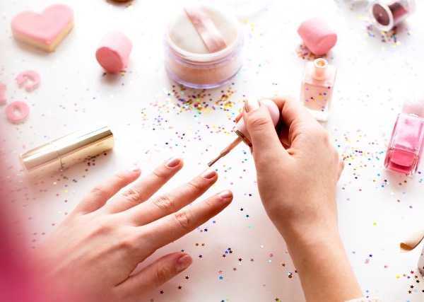 Woman with pink hair doing nail polish